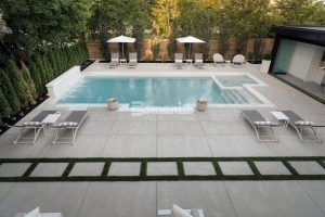 Longview from the house of a sleek backyard pool deck using the Bomanite Sandscape Refined Exposed Aggregate System with bands of grass installed by Bomanite Toronto in Canada.