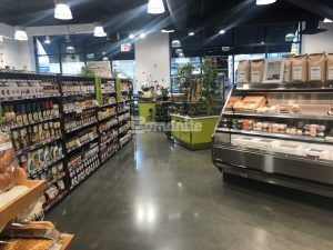 Flanked by a cold display unit and shelves a long view towards the street at Brothers Marketplace in Waltham, MA, featuring Bomanite Systems Custom Polished VitraFlor decorative concrete flooring installed by Premier Concrete Construction.